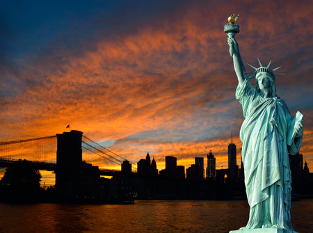 Estatua de la Libertad y Manhattan horizonte al atardecer.