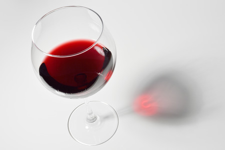 Wineglass with red wine on white background.
