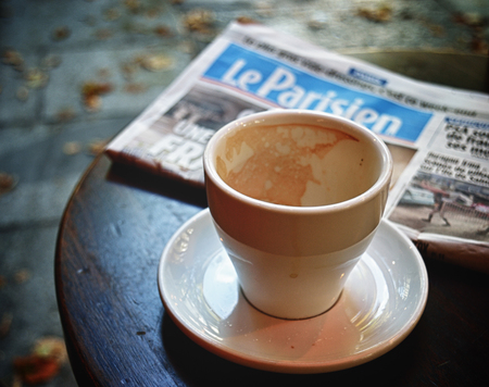 Paris, France - September 9, 2017: An empty coffee cup and Le Parisien newspaper on the cafe table.
