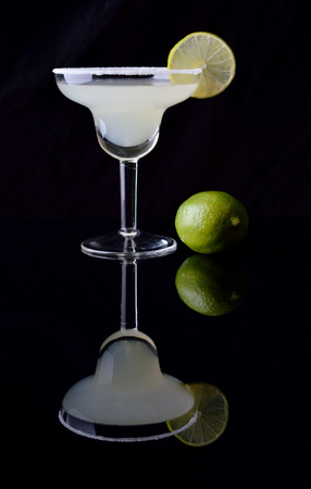 Margarita cocktail and lime on black background.