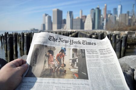 New York City, USA - February 3, 2019: The New York Times newspaper against a Lower Manhattan skyline.