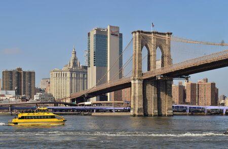 New York City, USA - February 3, 2019: New York Water Taxi ferry boat on the East River near the Brooklyn Bridge, Lower Manhattan. Sajtókép