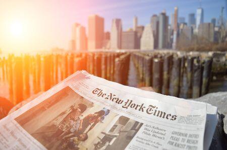 New York City, USA - February 3, 2019: The New York Times newspaper against a Lower Manhattan skyline.