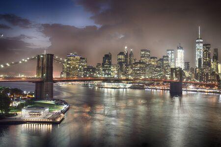 Twilight view of Lower Manhattan with Brooklyn Bridge.