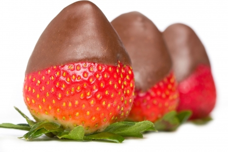 chocolate covered strawberries: Three delicious chocolate covered strawberries with green leaves. Stock Photo