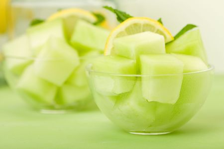 Cool cantaloupe melon cubes, ready for summer on orange in a glass bowl