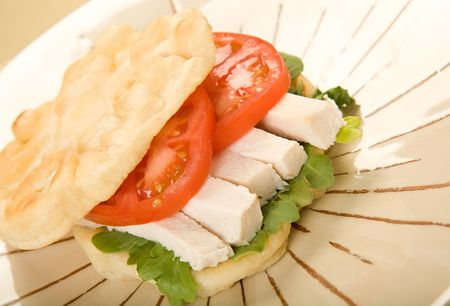 Roasted chicken on buttery flat bread with arugula and tomato Imagens