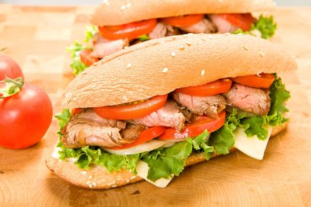 Sliced steak on submarine roll with lettuce, tomato, onion, and peppers