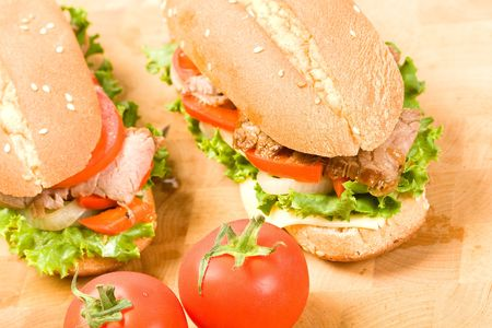 Sliced steak on submarine roll with lettuce, tomato, onion, and peppers photo
