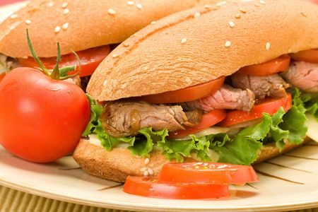 Sliced Steak Sandwich on plate with tomato photo