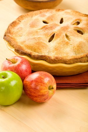 Whole apple pie in yellow baking dish on wood surface photo