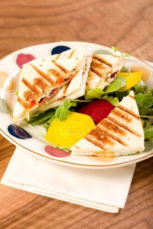 Chicken, bacon, pepper, pear and gouda panini with salad Фото со стока