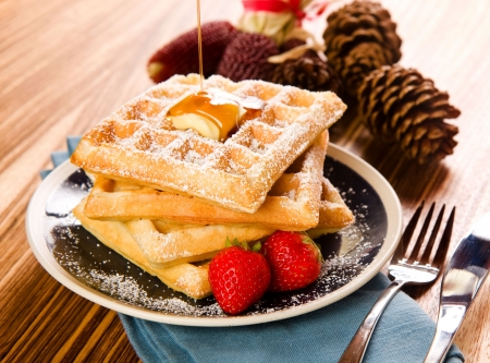 waffles: Crisp waffles with syrup in a warm fallwinter setting
