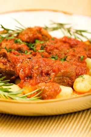 大きな肉の塊と豊富なラグーとニョッキをもみ消す