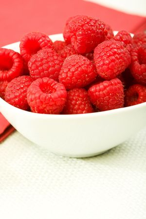 Red raspberries on textured light green tablecloth