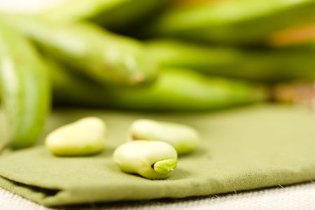 Three shelled fava beans with whole beans in backgrounds photo
