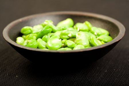 Fava beans in black bowl on Black textured fabric