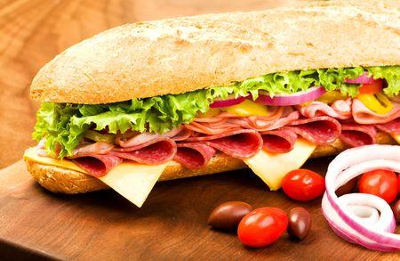 Footlong Salami, jambon, fromage sub avec la laitue, les tomates, les oignons et les poivrons Banque d'images - 5915458