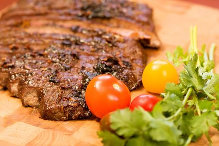 Whole Chipotle Grilled Flank steak on wood cutting board Stock Photo