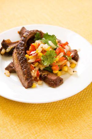 Slank steak on white plate with corn salsa