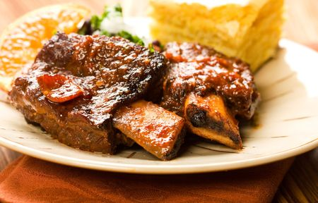 Tender braised beef ribs accompanied by black beans and cornbread