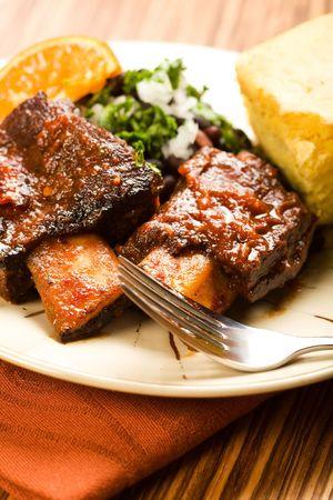 vergezeld: Tender gestoofd rundvlees ribben vergezeld van zwarte bonen en cornbread Stockfoto