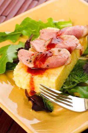 Rare duck served over polenta with salad