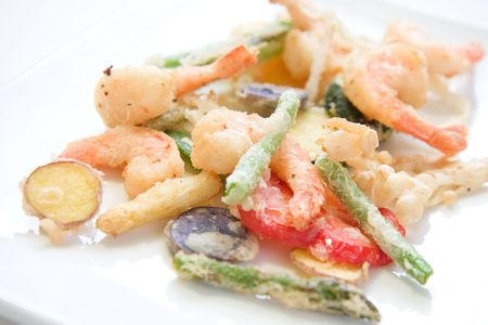Shrimp and a variety of tempura fried vegetables including potato, string bean, asparagus, and peppers Stock Photo