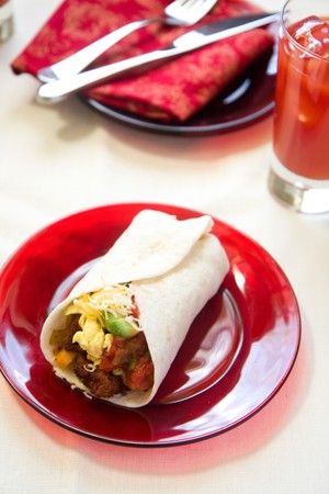 Spicy chorizo and salsa come together with eggs, potato, and avacado for a spicy breakfast accompanied by blood marys. photo