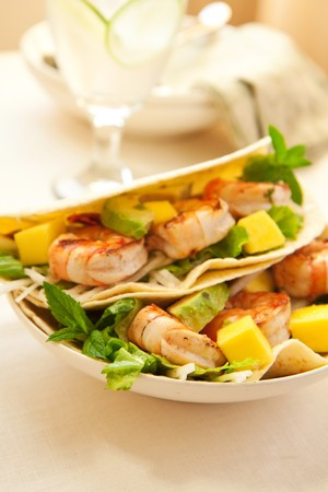 taco tortilla: Delicious Spicy shrimp taco with lettuce jimaca salad mano and avocado Stock Photo