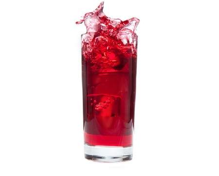An Ice cube splashes into cold cranberry juice photo