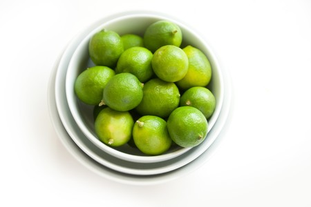 nested: Fresh key limes in nested white bowls Stock Photo