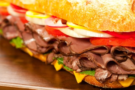 sandwich bread: Large roast beef sandwich with cheese, lettuce, tomatoes, onion, red and yellow peppers.