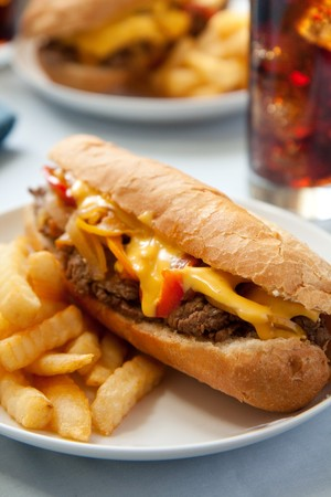 cheesesteak sandwich accompanied by fries and an ice cold cola Stock Photo