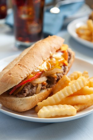 vergezeld: Cheesesteak sandwich vergezeld van frietjes en een ijskoude cola