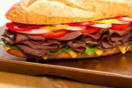 Grote rosbiefsandwich met kaas, sla, tomaten, ui, rode en gele paprika's.