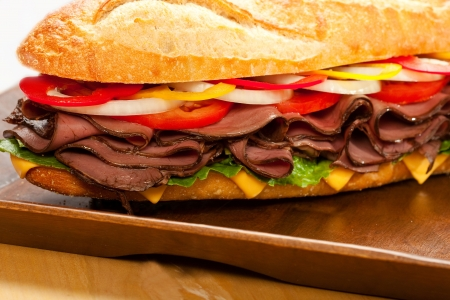 Large roast beef sandwich with cheese, lettuce, tomatoes, onion, red and yellow peppers.