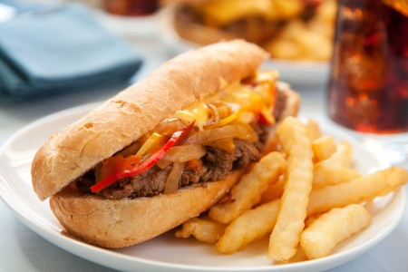 cheesesteak sandwich accompanied by fries and an ice cold cola photo