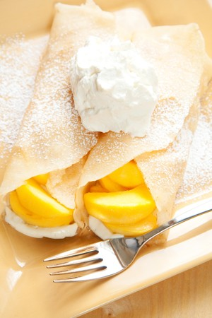 dollop: Peach crepes with a large dollop of whipped cream