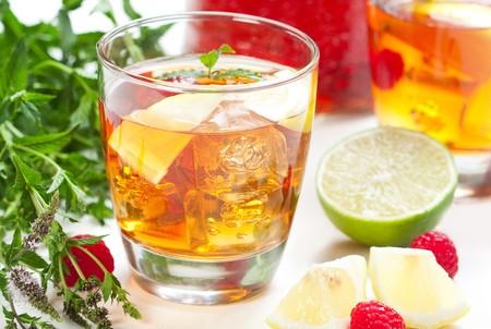 Iced tea accompanied by fresh flowering mint, lemon, lime and raspberry photo