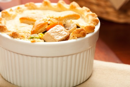 Turkey pot pie cut open to display tender turkey breast, carrots, mushrooms and peas Imagens