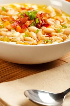 pancetta cubetti: Una zuppa di fagioli bianchi abbondante sormontato con pancetta e cipolla verde