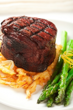 Thich Filet mignon served with crispy onions and asparagus Stock Photo
