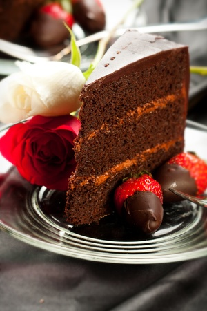 Rich dark choclate cake with mousse filling accompanied by chocolate covered strawberries and champagne Stock Photo - 8584892