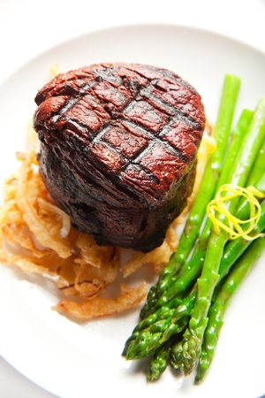 Thich Filet mignon served with crispy onions and asparagus photo
