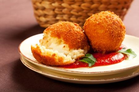 Diepe gebakken ballen van arborio rijst gevuld met mozzarella kaas