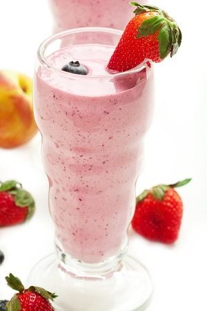 Berry smoothie accompanied by fruit in a vintage glass photo