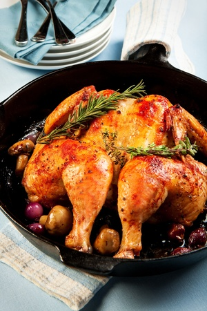 Whole chicken roasted in cast iron skilled with red pearl onions and mushrooms photo