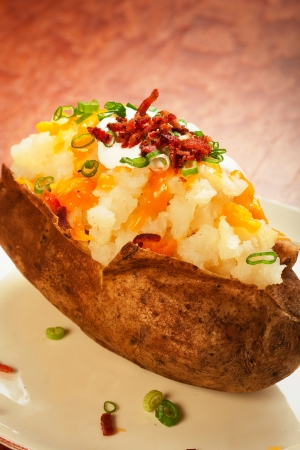 Baked potato loaded with cheese, green onion, sour cream, and bacon photo