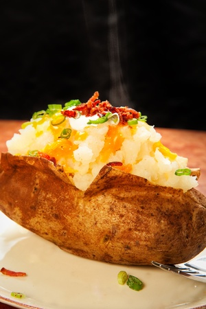 Steaming baked potato loaded with cheese, green onion, sour cream, and bacon